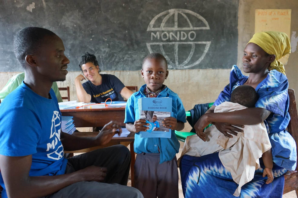 Student, baby, parents and teacher in classroom in Uganda, Bold Tuesday and Mondo charity