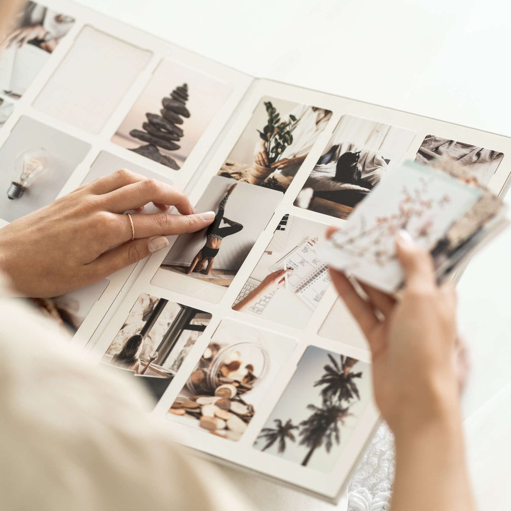 Woman's hands using open vision board with photos