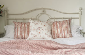 dusky pink wishbone and meadow flower cushions on a bed
