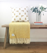 mustard hare cushion on a bench with yellow blanket