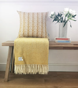mustard wishbone cushion and yellow blanket
