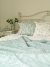 duckegg blue wool blanket and rebecca pitcher cushions on a bed