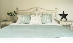 bedroom display of duckegg blue wool blanket and cushions
