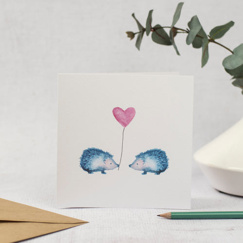 Blank Card featuring two blue hedgehogs holding a heart shaped balloon