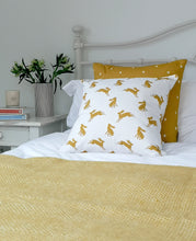 Load image into Gallery viewer, mustard and white hare and star cushions on a bed