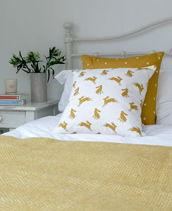 mustard and white hare and star cushions on a bed