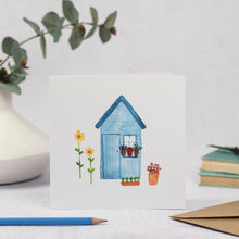blank card with watercolour painting of a blue shed and sunflowers