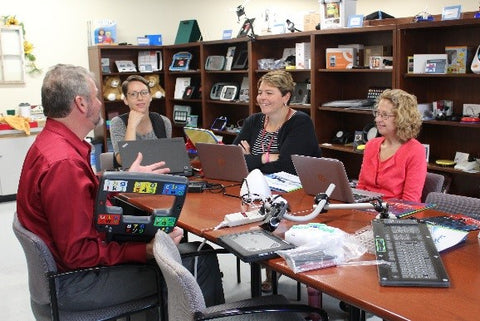 Members of the EASTCONN Assistive Technology team listen as Glen shares one of the LoganTech AAC devices; the Megabee®