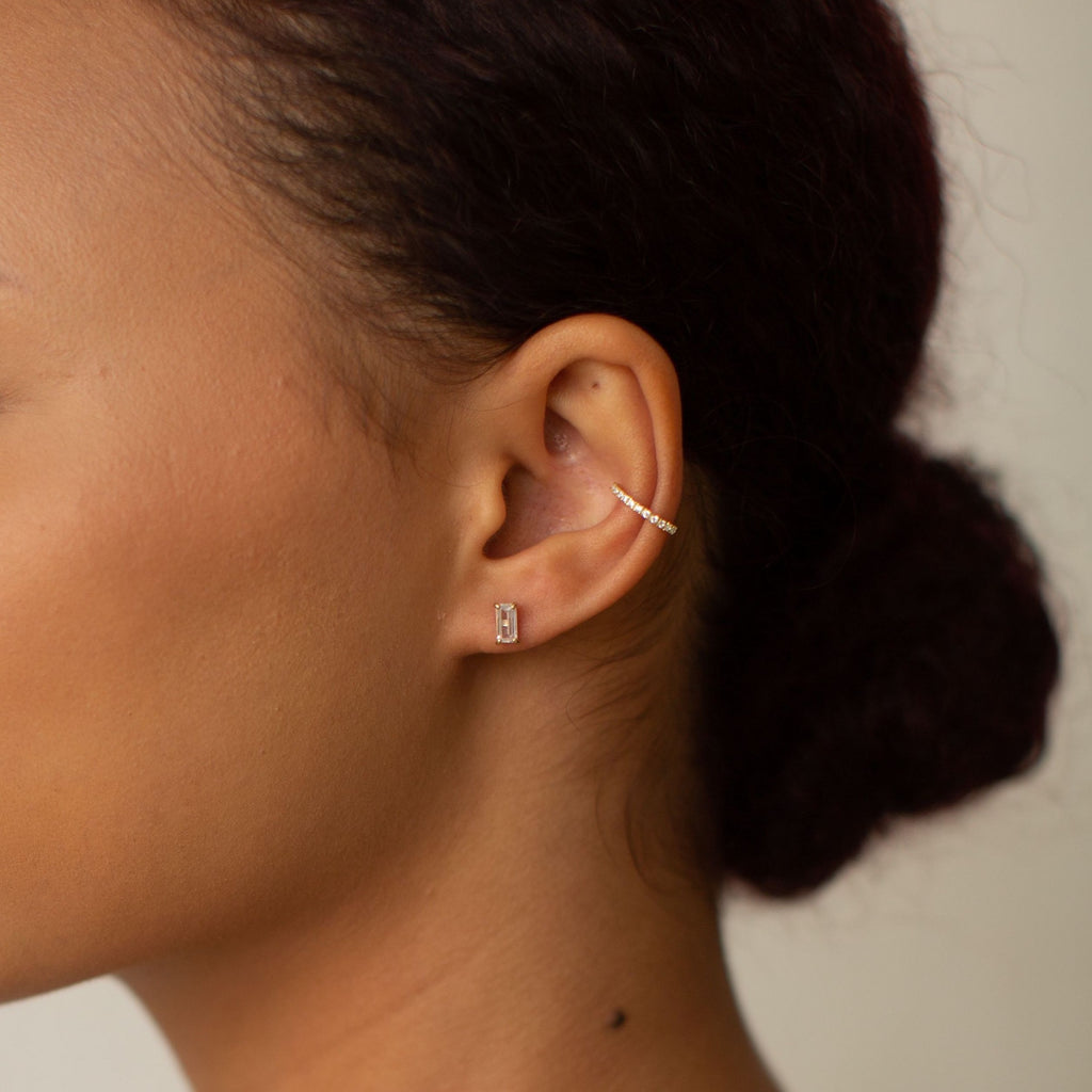 Model image of our 10k Solid Gold Emerald CZ Studs in yellow gold, paired with our CZ Prong Middle Ear Cuff.
