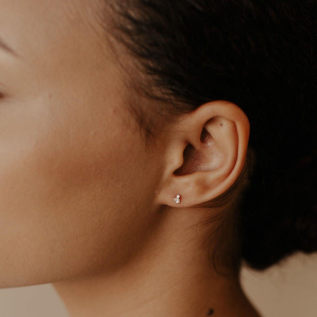 10k Solid Gold Tiny Round & Teardrop Cubic Zirconia Studs on model.