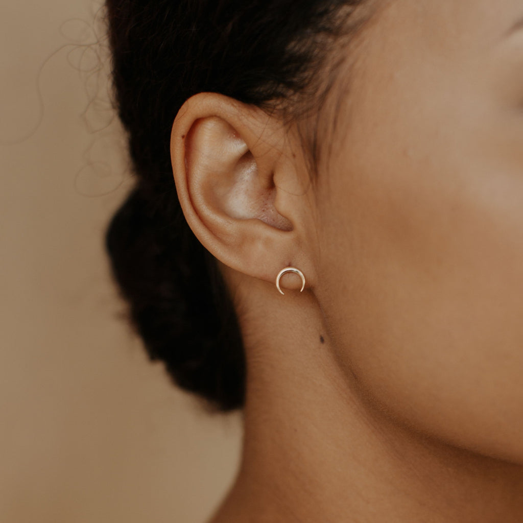 Model wearing our 10k Solid Gold Crescent Horn Studs in yellow gold.