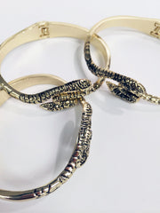 Cobra Gold plate snake bangle with hinged closure and textured metal.