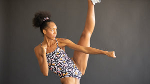 a woman doing a high kick wearing the starlight print one piece bathing suit