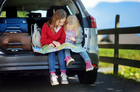 Two girls sit together and look at a map on a road trip