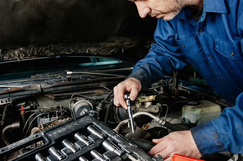 A mechanic works to repair a part under the hood of a car