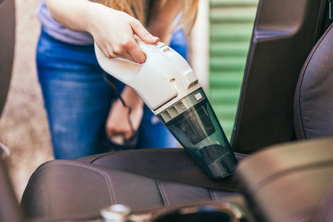 woman cleaning vehicle with car vacuum