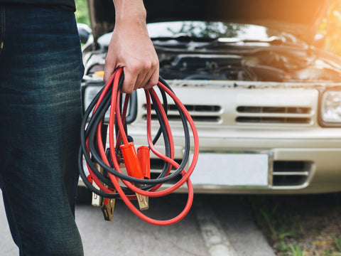 man holding jumper cables with broken down car in background