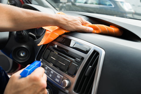 person cleaning car dashboard