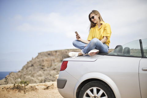 A woman uses her phone on a road trip after charging it with her car phone charger