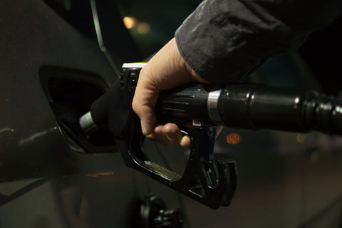 A man fills up on gas at the pump — is he saving money with good gas mileage?