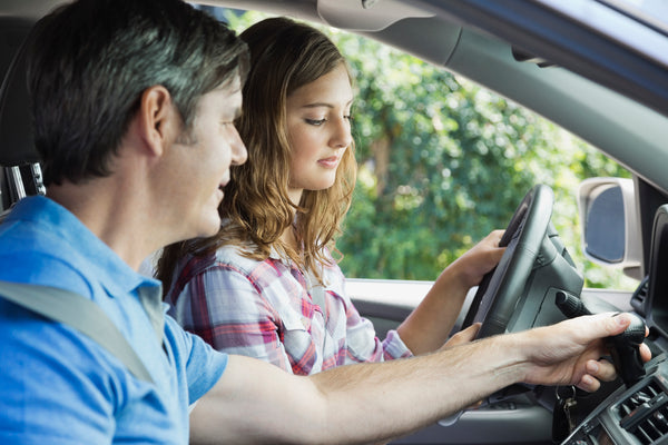 A dad teaches a teen driver in her first car