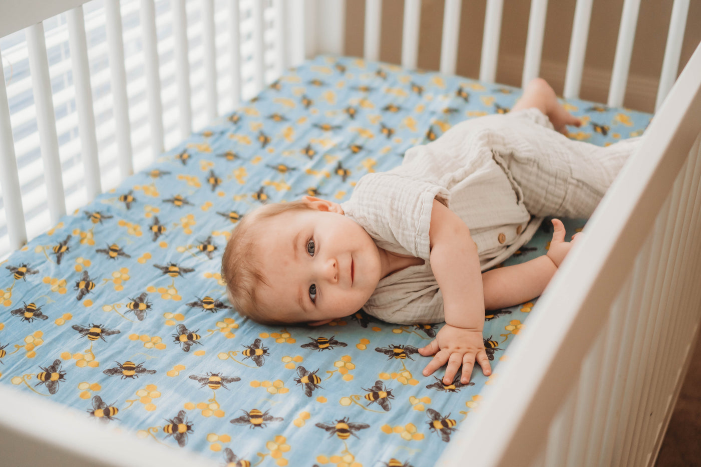 Baby with blue bee and honeycomb boho vintage crib sheet in nursery