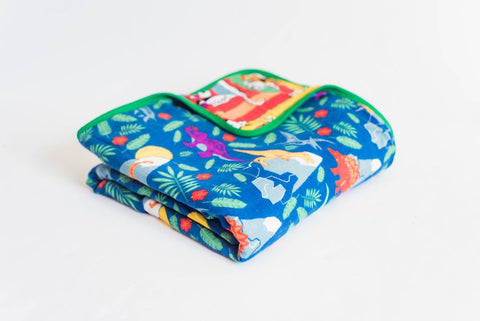 Zoomed out, angled view of bamboo muslin rainbow dinosaur royal blue toddler baby blanket.  Bedding with purple, yellow, red, orange, and green in a gender neutral style for girls or boys.