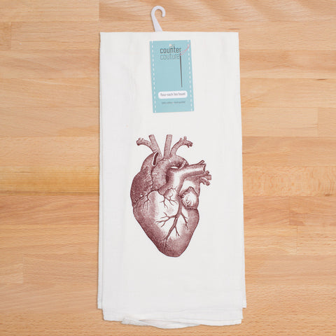 Singular red anatomical heart on white tea towel.