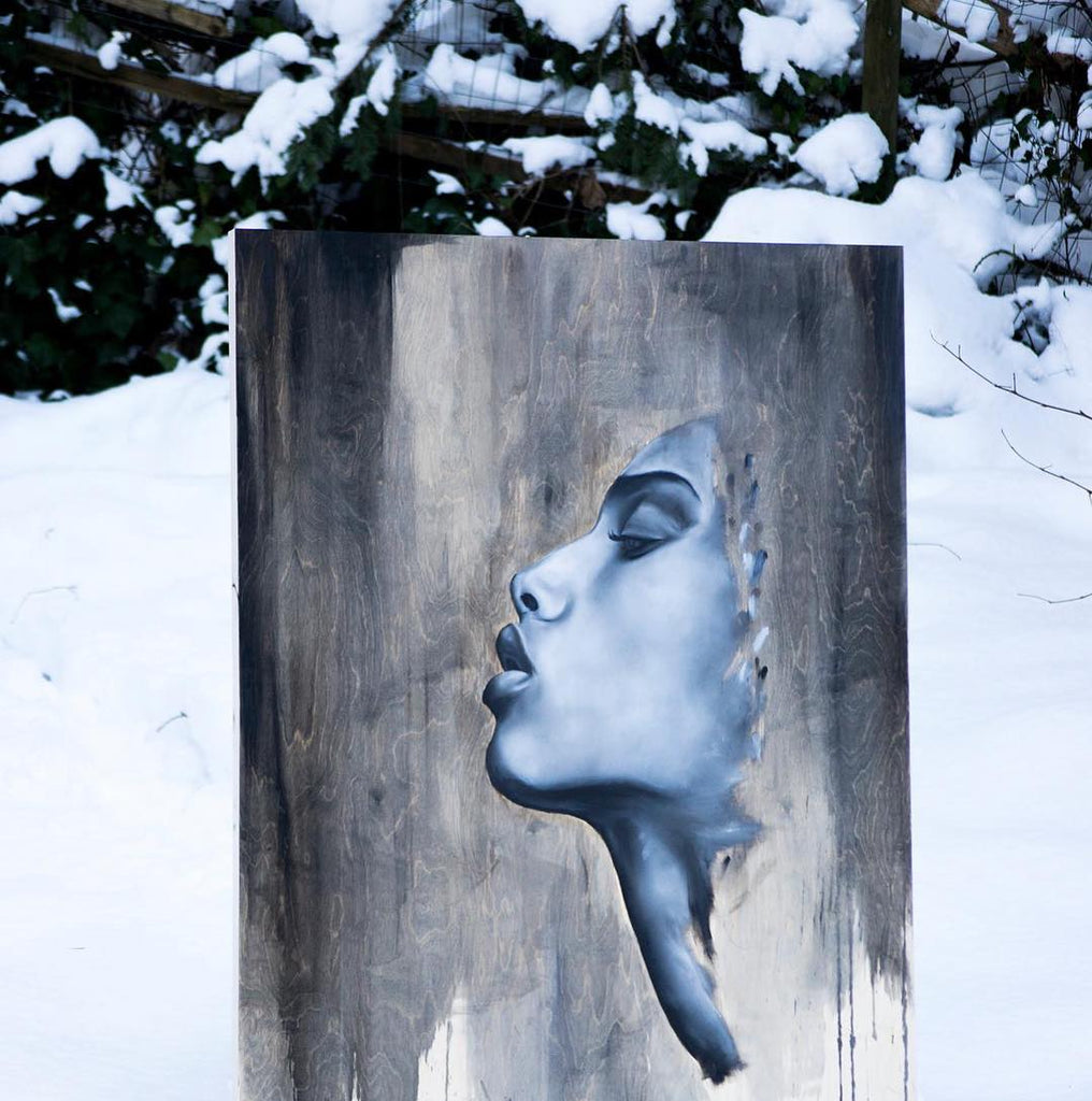 painting of woman's face on wood surface, painting is staged in the snow