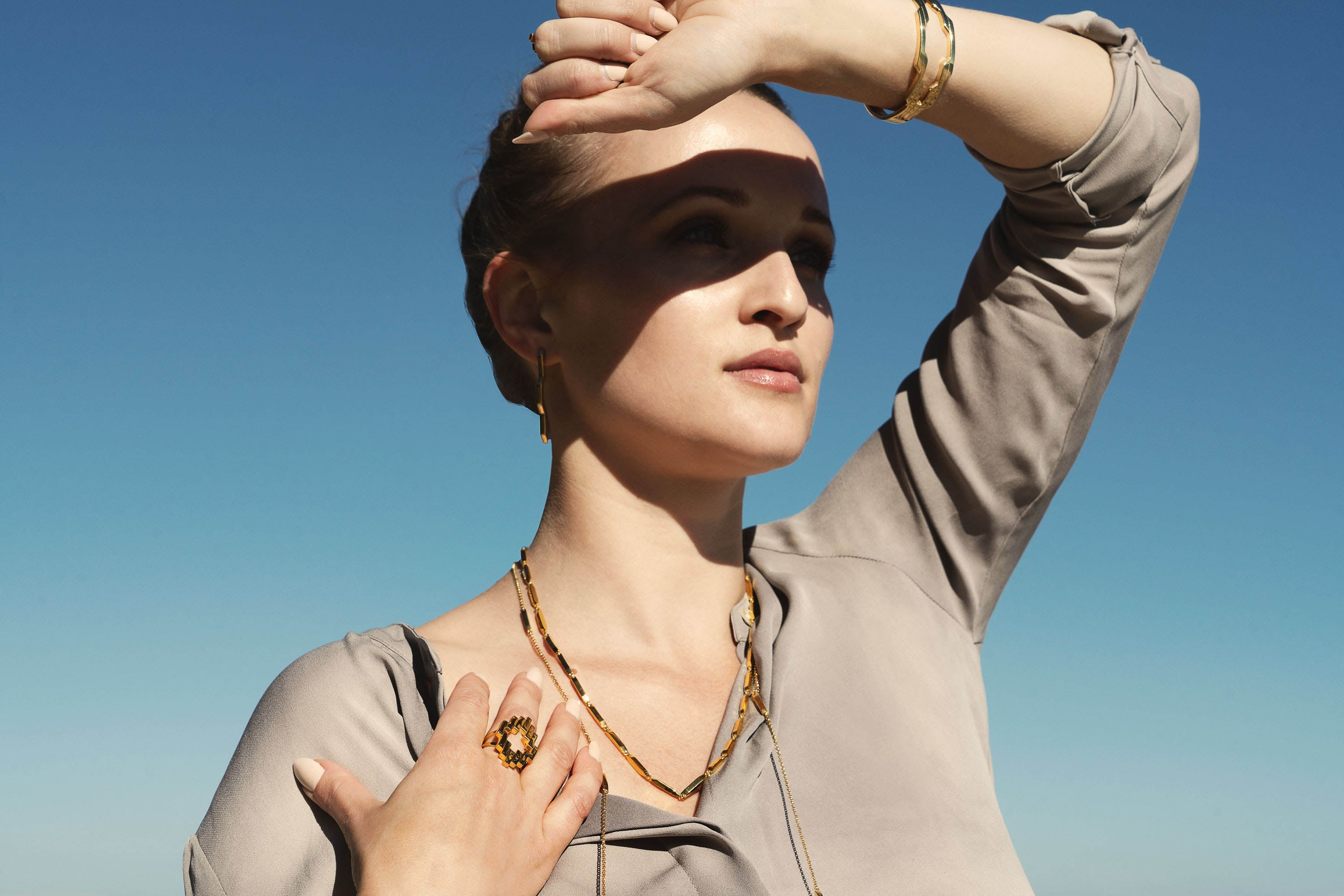 Founder and Designer Cat Janiga blocking her eyes from the sun, wearing the jewelry collection CORONA and SOL.