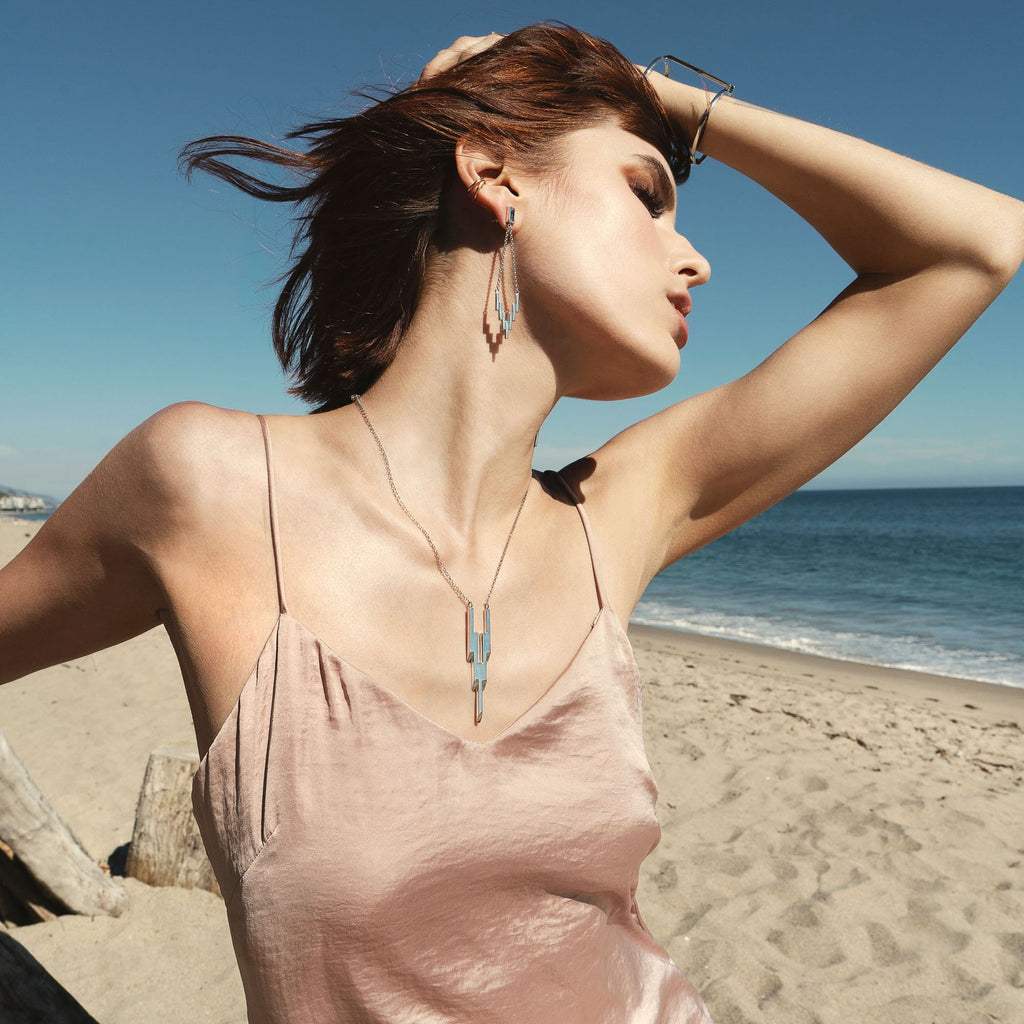 Woman on beach wearing Cat Janiga Jewelry After Glow Collection