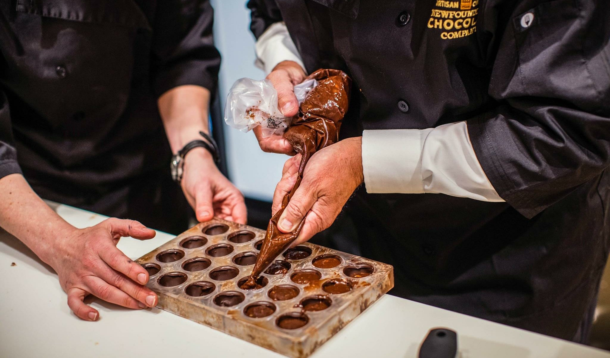 Shot from the shoulders down. A person fills a mold with chocolate using a piping bag. A second person holds the edge of the mold.