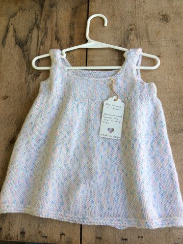 Hand-Knitted White and Pastel-Flecked Baby Girl Dress by Joanna Izzard