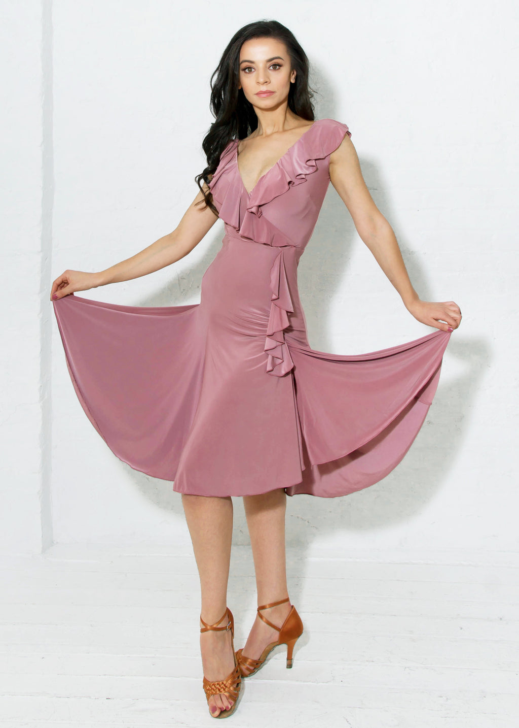 Miari latin ballroom dress in dusty rose with flirtatious V-neckline in both the front and back with a cascading asymmetrical ruffle and a slit on the dancer's left side.
