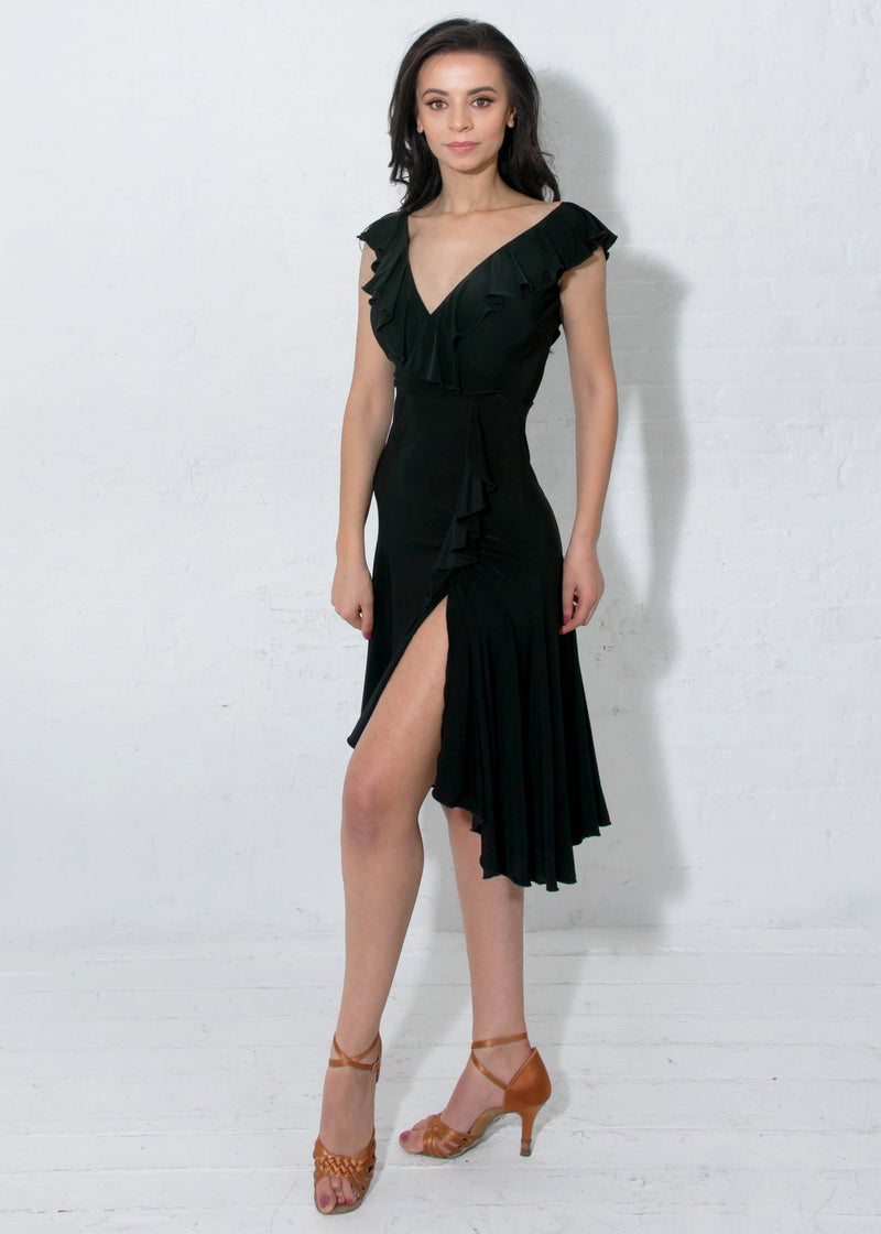 Black latin dress with flirtatious V-neckline in both the front and back with a cascading asymmetrical ruffle and a slit on the dancer's left side.