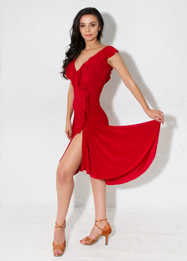 Miari red latin ballroom dress with flirtatious V-neckline in both the front and back with a cascading asymmetrical ruffle and a slit on the dancer's left side.