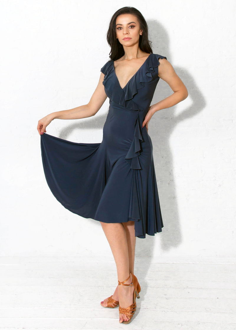Miari steel color latin ballroom dress with flirtatious V-neckline in both the front and back with a cascading asymmetrical ruffle and a slit on the dancer's left side.