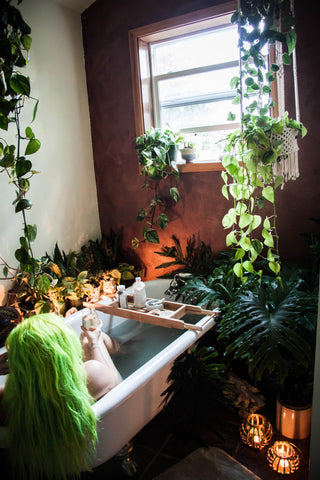 woman in bathtub with plants