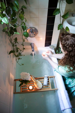 woman lighting candle above bathtub