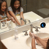 Two young girls, ages 6 and 7, have fun and smile while washing their hands in a bathroom setting. The Time Timer WASH visual timer for handwashing sits on the counter beside the sink.