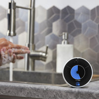 The Time Timer WASH visual handwashing timer sits on the granite countertop of a modern kitchen. In the background, an adult washes their hands.