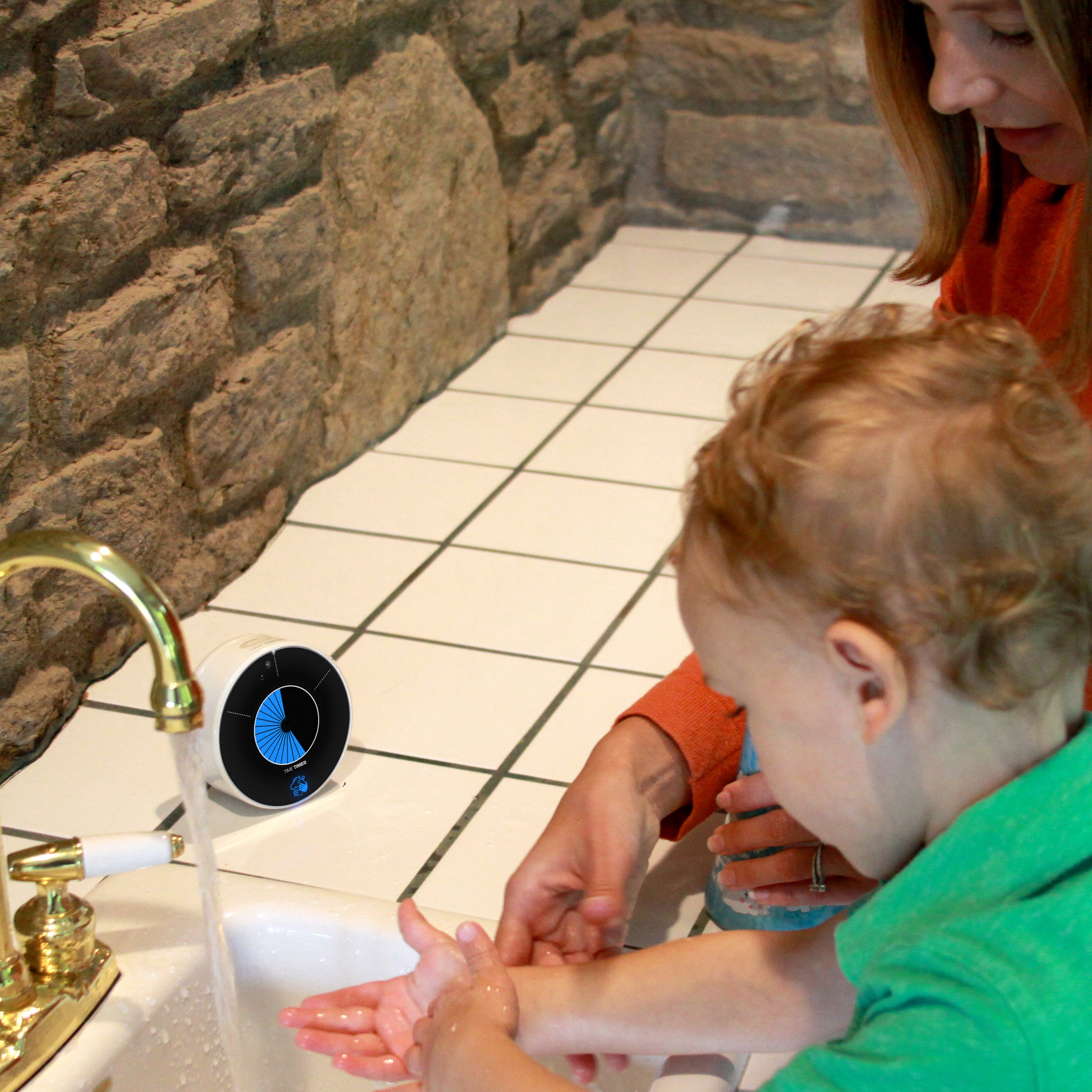 A mother or teacher helps a young toddler wash his hands at the sink by utilizing the Time Timer WASH visual timer for handwashing.