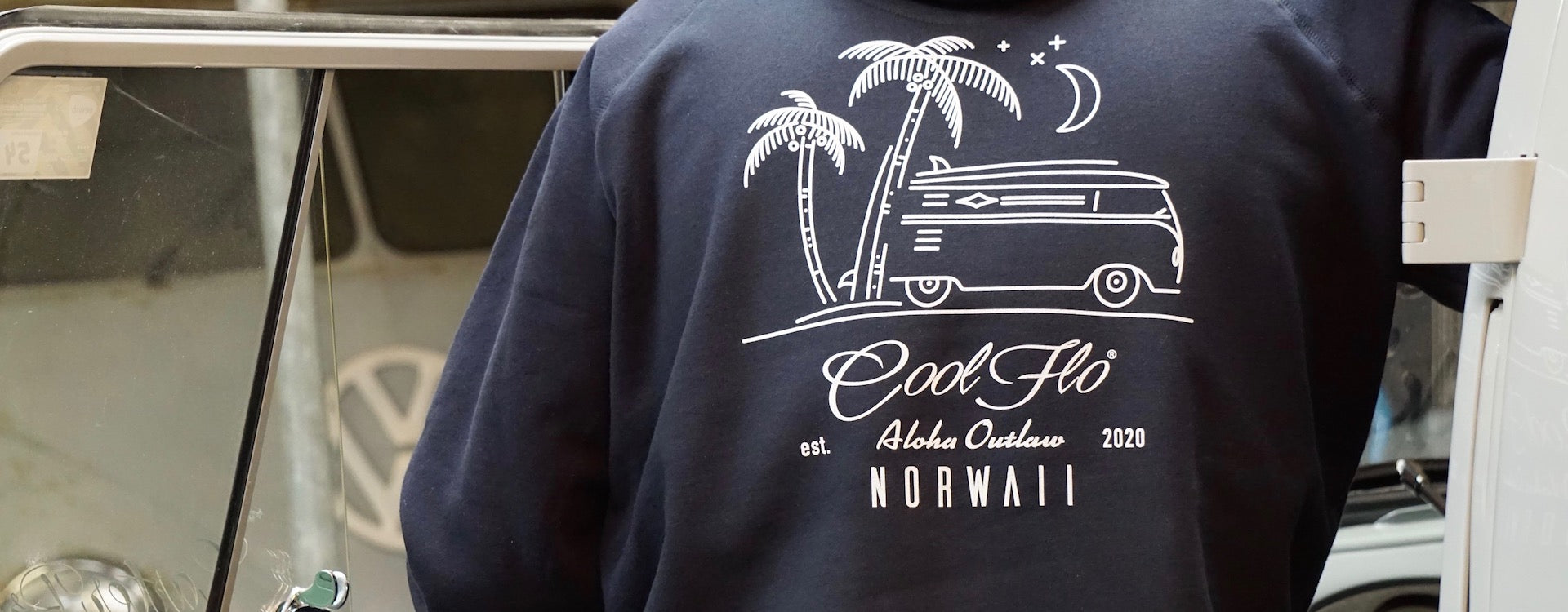 Back of model wearing Outlaw Bus navy hoody by the open door of a VW bus