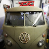 Cool Flo banner on the wall of a workshop behind a split-screen VW campervan
