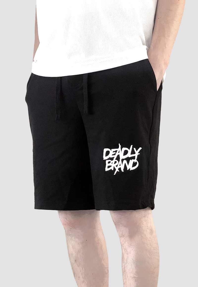 DEADLY BRAND® TRASHY logo embrodiered in white on the front of a pair of black shorts