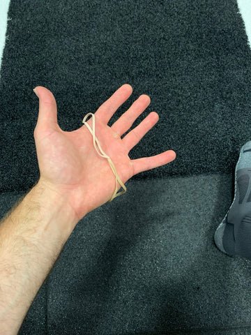 Using rubber bands to help maintain tension in the big toe when squatting barefoot