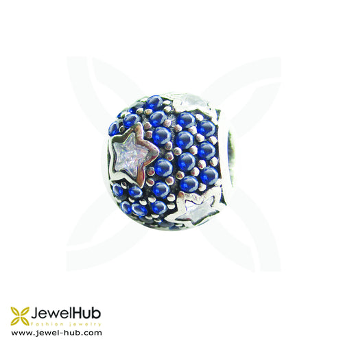 A delicately wrought charm with embedded crystals stars and dark blue crystals.