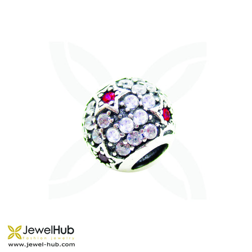 A delicately wrought charm with embedded red and white crystals.