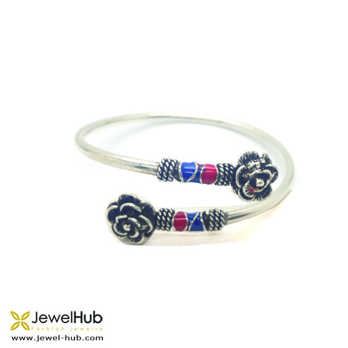 Flowers with small oxidized beads on i its sides rest gracefullyn the silver bangle.