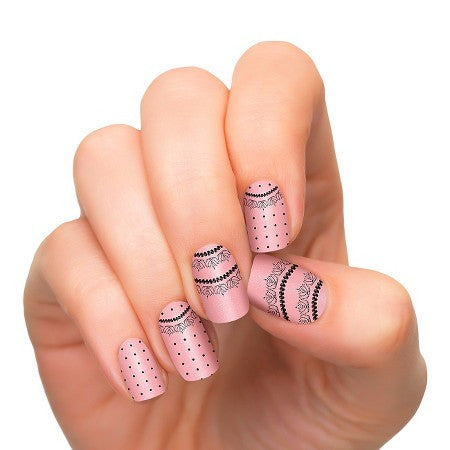 Nail polish strips with black laces in pink background.